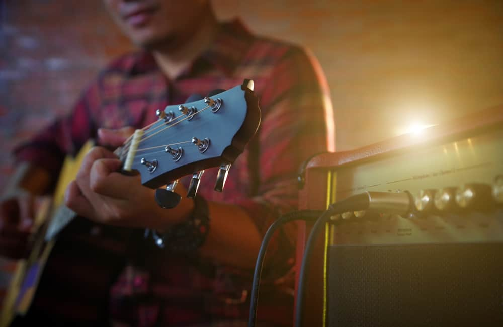 Guitarist playing guitar with amp
