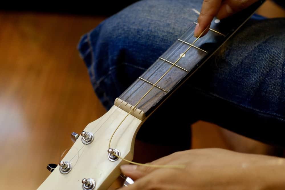 man changing acoustic guitar strings